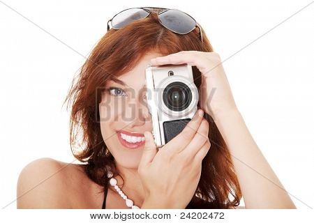 Young beautiful smiling woman holding a micro four thirds photo camera. Isolated over white background.