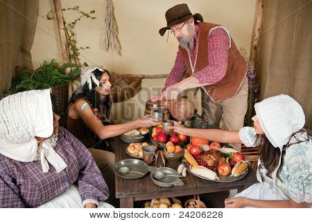 Reenactment scene of the first Thanksgiving Dinner in Plymouth in 1621 with a Pilgrim family and a Wampanoag Indian