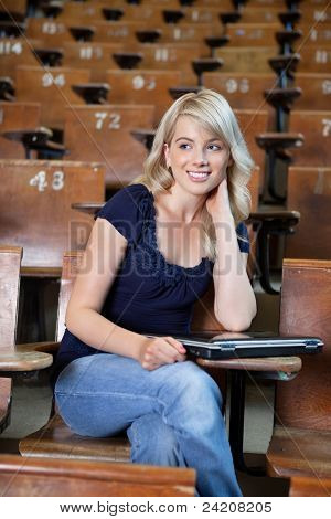 Portrait of a young happy college girl in lecture hall with a laptop