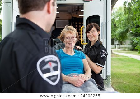 Two ambulance workers pushing a happy femaile patient