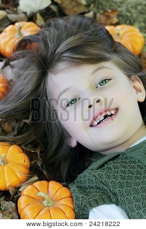 Child Lying In Autumn Leaves