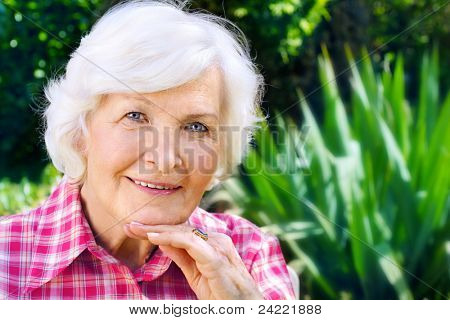 Senior woman portrait, outdoor, in front of the garden,smiling to camera