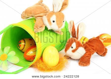 Two soft toy easter bunnies  playing with an easter egg, isolated on white background