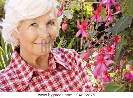 Senior woman portrait, outdoor, in front of the garden ,beside a beautiful flower,smiling to camera