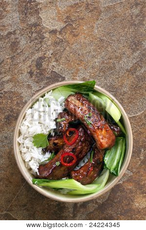 Barbecued pork spareribs with rice and Asian greens.