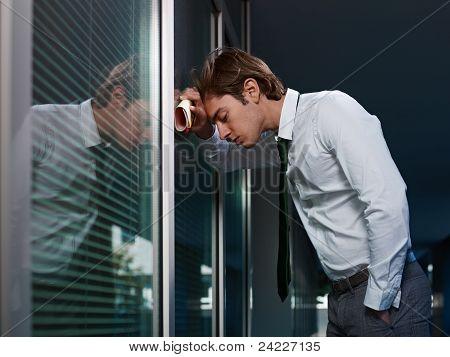sad businessman leaning on window in office