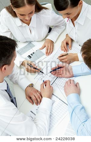 High angle view of four businesspeople working with financial data