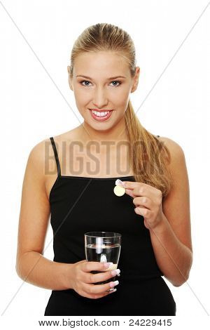 Happy young blond woman putting pill into glass full of water (diet supplement)