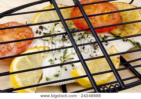 Plaice In A Fish Grill With Tomato And Lemon