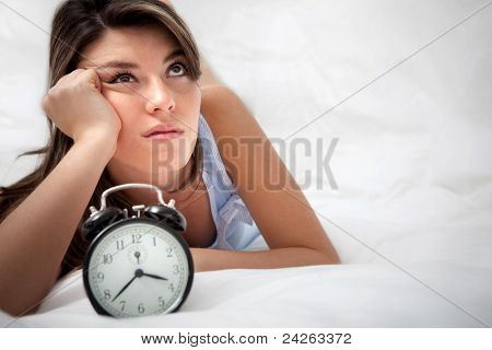Sleepless woman lying in bed looking at the hours pass by