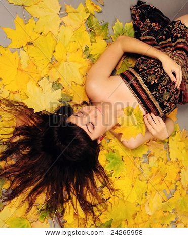 Brunette girl portrait lying in autumn leaves.