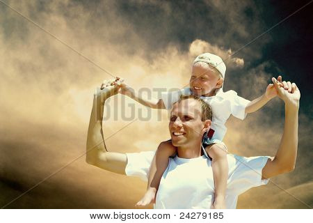 Joyful father giving piggyback ride to his son against a sky background