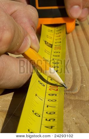 Worker Measuring Wood