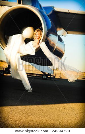 sexy young adult wedding model laying inside the engine intake of Boeing passenger aircraft