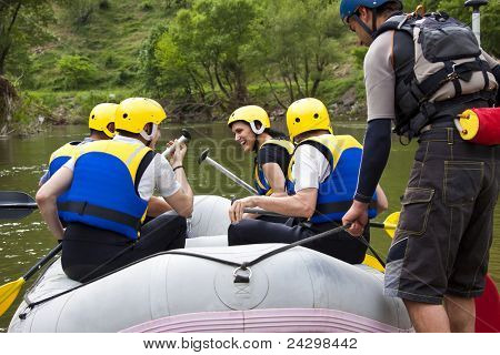 Group of young people sitting in a boat, getting ready for whitewater rafting