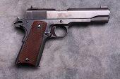 .45 caliber 1911 semi automatic pistol.  Vintage 1911 .45 caliber pistol on blue grey leather backgr poster