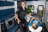 foto of triage  - Female EMT professional in ambulance with senior woman patient - JPG