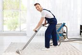 Male Worker Removing Dirt From Carpet With Professional Vacuum Cleaner Indoors poster