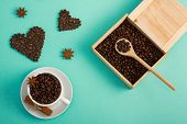Cup Of Coffee Seeds, Cinnamon, Anis Coffee Heart Shapes, Wooden Box And Spoon With Coffee    On Cyan poster