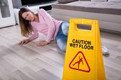 Mature Woman Falling On Wet Floor In Front Of Caution Sign At Home poster