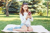 Portrait Of Young Worried Caucasian Teenage Girl With Her Phone Outside In Park. Serious Stressed Wo poster