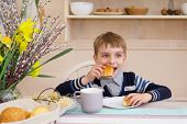 Little Boy Having Breakfast In The Kitchen. The Boy Is Eating A Croissant. Breakfast Table With Boy. poster