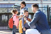 Young Parents Saying Goodbye To Their Little Children Near School poster