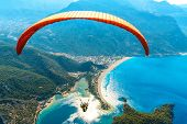 Paragliding In The Sky. Paraglider Tandem Flying Over The Sea With Blue Water And Mountains In Brigh poster
