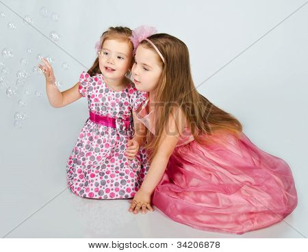 Two Cute Little Girls Looking Soap Bubbles