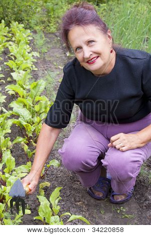 The happy smiling woman works on a garden site