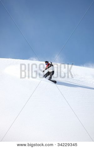 A snowboarder gliding down a slope