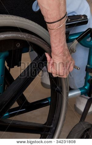 Close-up of Elderly Woman's Hands on wheelchair.