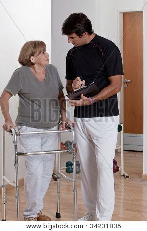 Patient with walker discusses his progress.