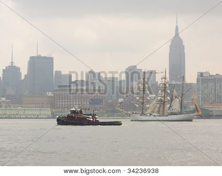 HOBOKEN, NJ - MAY 23: The tugboat Ellen McAllister travels past a tall ship near  Manhattan during the Parade of Sails on May 23, 2012 in Hoboken, NJ. The parade marks the start of Fleet Week.