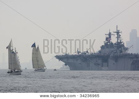 HOBOKEN, NJ - MAY 23: The USS Wasp (LHD 1) sails past tall ships on the Hudson River near Manhattan during the Parade of Sails on May 23, 2012 in Hoboken, NJ. The parade marks the start of Fleet Week.