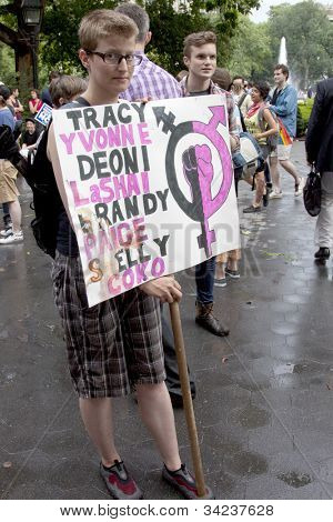 NEW YORK - JUNE 22: A supporter in Washington Square Park holds a sign that lists names of transgendered people who have died on the 8th Annual Trans Day of Action on June 22, 2012 in New York City.