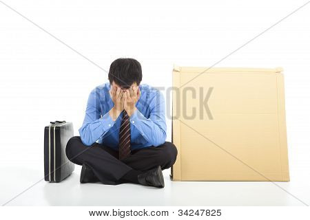 frustrated businessman sitting on ground and blank cardboard