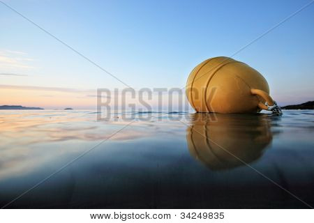Yellow buoy floating on the ocean waterline view