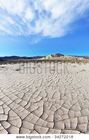 Cold morning in the desert. Cracked clay - takyr - surrounds a huge sandy dune Eureka