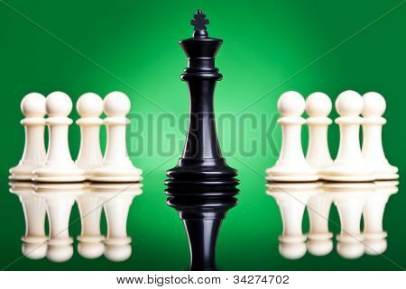 chess pieces - black king in front of white pawns - leadership concept