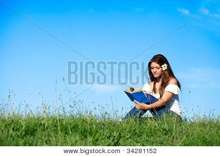 Pretty girl reading book and relaxing on grass with beautiful blue sky