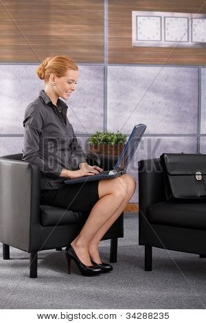 Happy businesswoman sitting in office armchair working on laptop computer, smiling. Full length side view portrait.