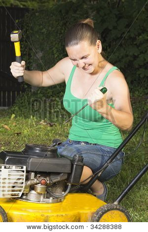 Angry girl breaking in pieces old lawn mover