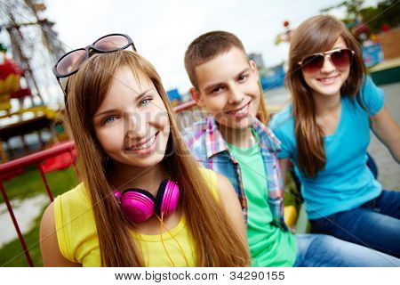 Teenagers spending time in the amusement park looking at cam with a smile