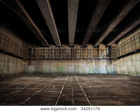 Huge stone and concrete space with tiled floor and ceiling of concrete beams.