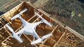 Unmanned Aircraft System Quadcopter Drone In The Air Over Construction Site. poster