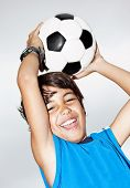 Happy jumping boy, cute kid playing football, active child, young male teen goalkeeper enjoying spor