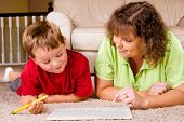 Mother helping child with writing lesson for school while at home