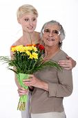 stock photo of get well soon  - Young woman giving a senior lady a bunch of flowers - JPG