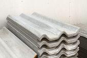 pic of asbestos  - Stack of gray asbestos roof in warehouse - JPG
